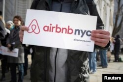 "FILE - Supporters of Airbnb stand during a rally before a hearing called ""Short Term Rentals: Stimulating the Economy or Destabilizing Neighborhoods?"" at City Hall in New York, Jan. 20, 2015."