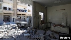 FILE - A general view shows damage at a site hit by airstrikes on Tuesday in the town of Khan Sheikhoun in rebel-held Idlib, April 5, 2017.