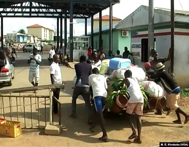 Youths push goods from Cameroon through the border to Equatorial Guinea, June 5, 2018.