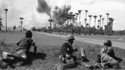 Cambodian soldiers await the end of an airstrike by U.S. planes in the background before advancing toward a palm grove off route 4, south of Phnom Penh, June 13, 1973. (AP photo)