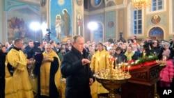 Presiden Rusia Vladimir Putin (tengah) menghadiri misa Natal Ortodoks di desa Turginovo, 150 kilometer, Rusia (6/1).