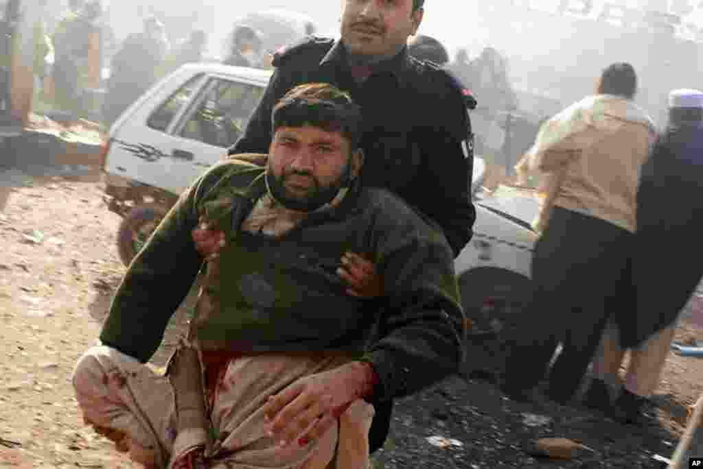 A member of the security personnel carries an injured person to a vehicle after an explosion in Pakistani tribal area of Khyber near Peshawar, Pakistan, January 10, 2012.