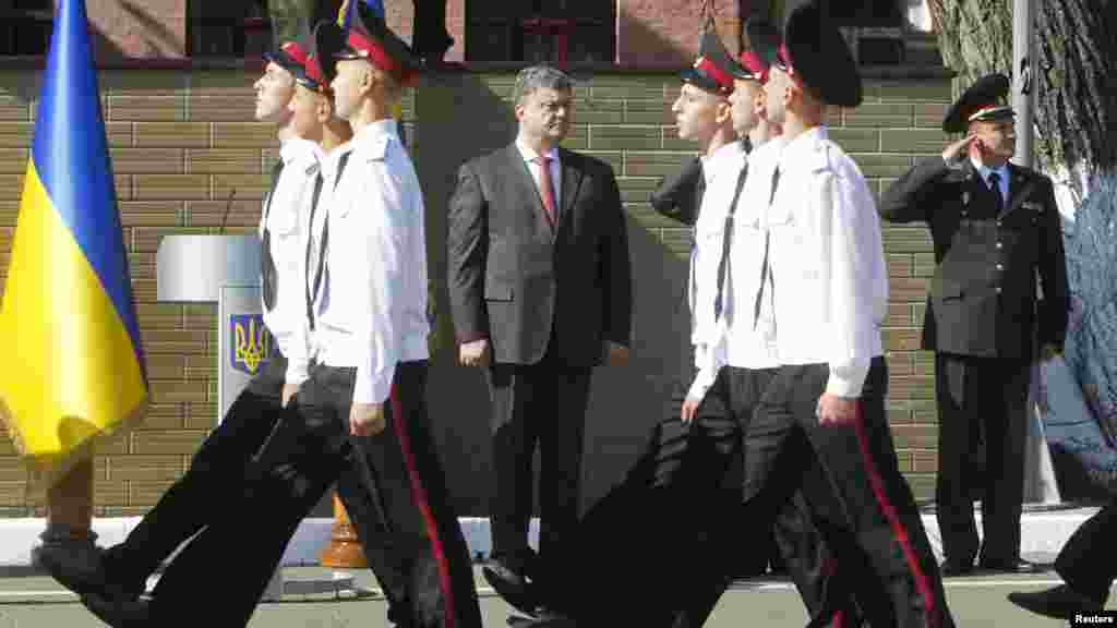 Ukrainian President Petro Poroshenko watches cadets as they march during Knowledge Day celebrations in Kyiv, Sept. 1, 2014.