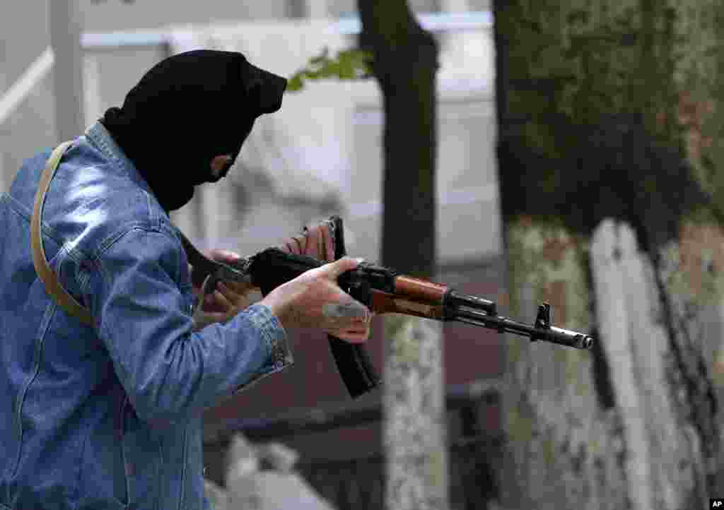 A pro-Russian gunman holds his weapon while guarding the local administration building in the center of Slovyansk, May 6, 2014.