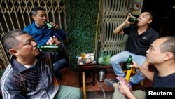 FILE - Men drink Sabeco's Saigon beer at a roadside restaurant in Hanoi, Vietnam, Nov. 29, 2017.