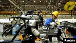 An employee works on an automobile assembly line at a factory in Qingdao, Shandong province, China, March 1, 2016. Activity in China's manufacturing sector shrank more sharply than expected in February.