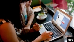 Two women use social networking site Tumblr in a cafe in Hanoi. (File)
