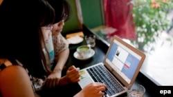 Deux femmes consultent une page Internet dans un café à Hanoi, Vietnam, 02 Septembre 2013. epa/ LUONG THAI LINH