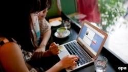 Two women use social networking site Tumblr in a cafe in Hanoi