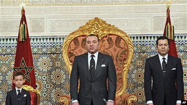 In this photo released by the Royal Palace, Morocco's King Mohamed VI flanked by his son Moulay El Hassan, left ,and his Brother Prince Moulay Rachid, right , listens to the national anthem after he delivered a speech to the nation, March, 9, 2011, at the