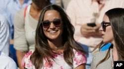 FILE - Pippa Middleton, left, the sister of Kate, the Duchess of Cambridge, watches the quarterfinal tennis match between Canada's Milos Raonic and France's Gilles Simon on the fifth day of the Queen's Championships in London.