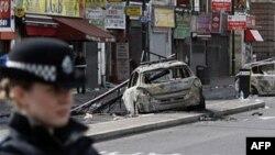 Cảnh sát canh gác tại hiện trường ở Tottenham, nơi các chiếc xe cảnh sát bị đốt cháy, ngày 7/8/2011