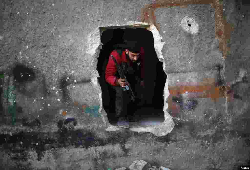 26일 알레포 지역에서 정부군과 반군간 충돌이 계속되는 가운데, 벽에 뚫린 통로를 통해 빠져나오는 반군 병사.