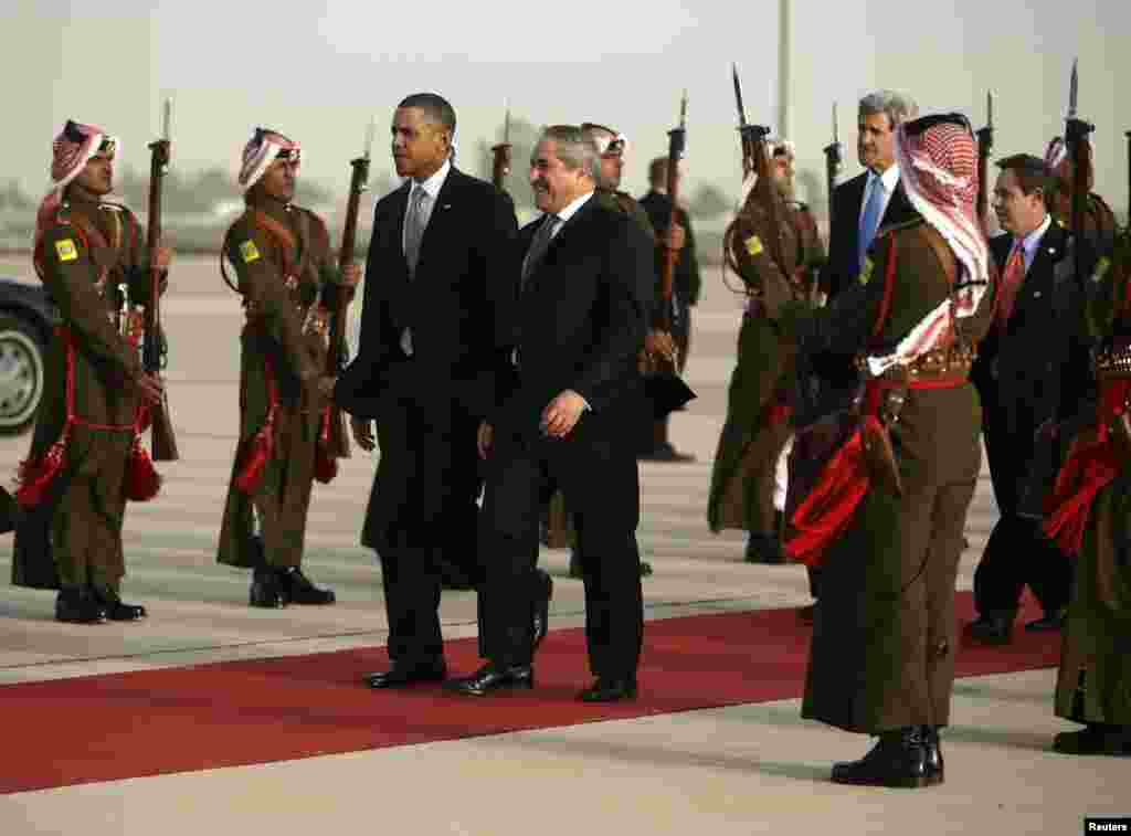 U.S. President Barack Obama walks with Jordanian Foreign Minister Nasser Judeh, right, upon his arrival at Queen Alia International Airport in Amman, Jordan, March 22, 2013.