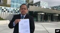 جود حوزو سابیو، وکیل فیلیپینی، در مقابل ساختمان دادگاه لاهه در هلند شکایتنامه خود از دوترته را نشان می دهد