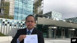 FILE - Lawyer Jude Sabio from the Philippines holds a 77-page file outside the International Criminal Court in The Hague, Netherlands, April 24, 2017. Sabio presented the file to prosecutors and asked to investigate his country's president Rodrigo Duterte for crimes against humanity for his alleged involvement in extrajudicial killings of suspected drug dealers and other crime suspects.