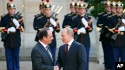 Presiden PerancisFrancois Hollande (kiri) menyambut Presiden Rusia Vladimir Putin saat tiba di Istana Elysee Palace, Paris (5/6). (AP/Francois Mori)