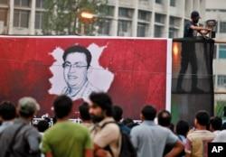 FILE - A Bangladeshi activist sets up a light on a poster displaying a portrait of slain Bangladeshi-American blogger Avijit Roy in Dhaka, Bangladesh, Feb. 27, 2015.