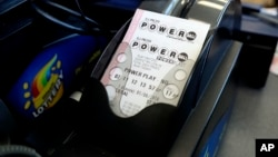 A Powerball lottery tickets are printed out of a lottery machine at a convenience store, Jan. 6, 2018, in Chicago.