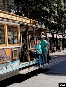 Tourists ride on a cable car in San Francisco, California, April 6, 2016. (M. O'Sullivan/VOA)