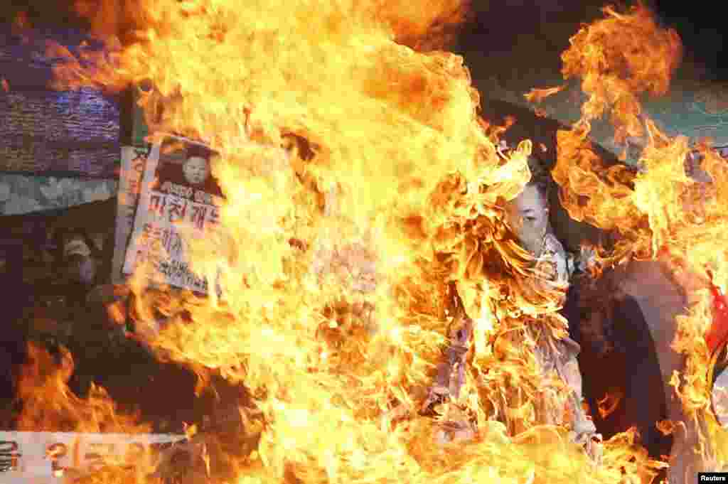 Anti-North Korean protesters burn an effigy of North Korea's leader Kim Jong-Un and its flag during a protest blaming the North's rocket launch in central Seoul December 12, 2012. North Korea successfully launched a rocket on Wednesday, boosting the crede
