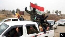 Les combattants chiites des Forces de Mobilisation Populaire patrouillent dans un quartier récemment libéré des mains de militants du groupe Etat islamique dans l'est de Mosul, Irak, 25 janvier 2017.