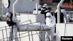 Para penjaga pantai Italia berpakaian pelindung membawa jenazah imigran dari kapal Bruno Gregoretti, di Senglea, pelabuhan Valetta, Italia (20/4). (Reuters/Darrin Zammit Lupi)