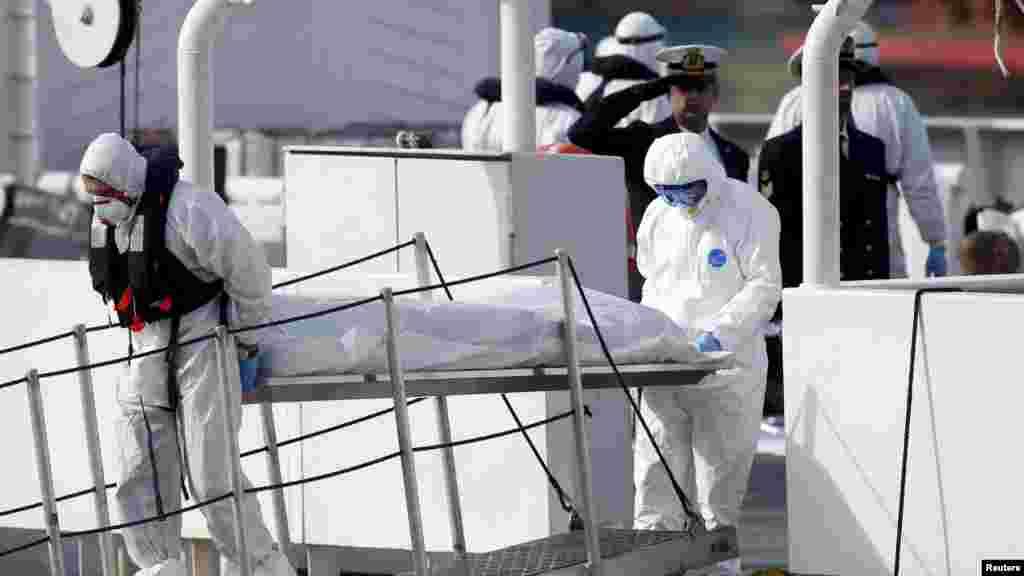 Des agents de la Garde côtière italienne, couverts de vêtements de protection, transportent le corps d'un immigrant mort, hors de leur navire Bruno Gregoretti, à Senglea, à La Valette Grand Harbor, le 20 avril 2015.