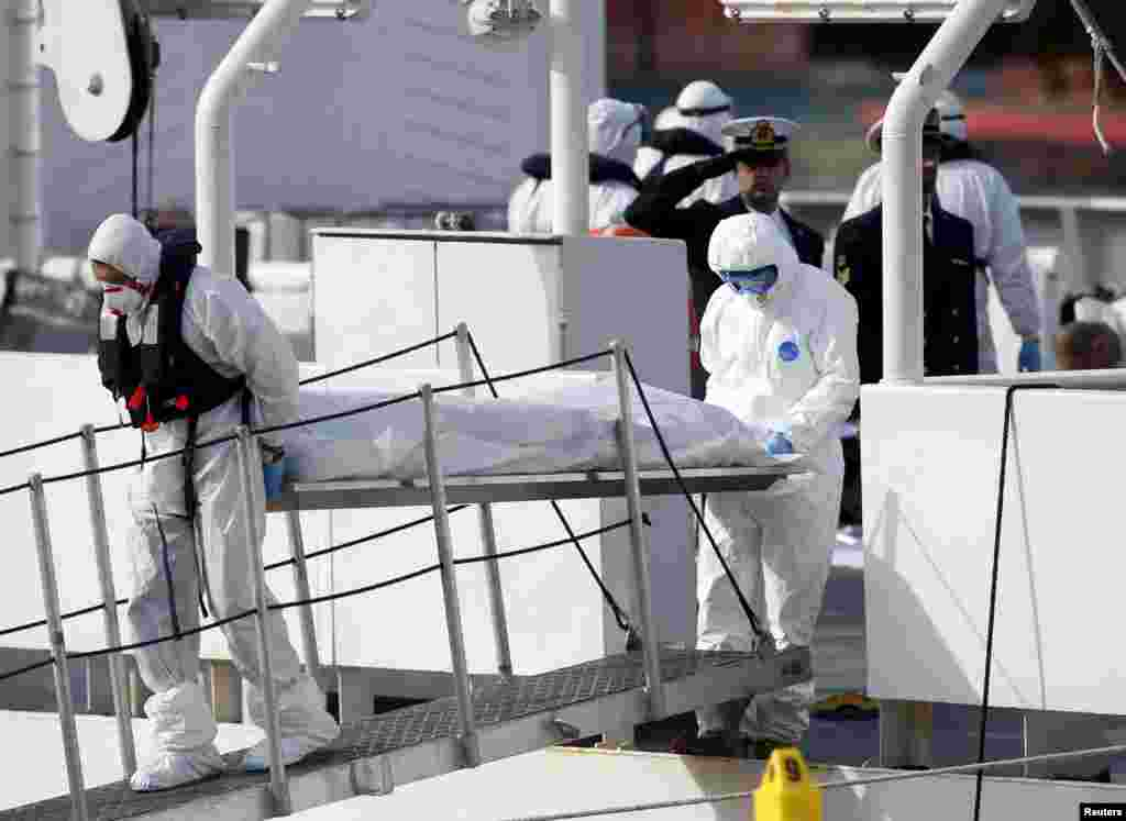 Italian Coast Guard personnel in protective clothing carry the body of a dead immigrant off their ship, Bruno Gregoretti, in Senglea, in Valletta's Grand Harbor, April 20, 2015.