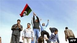 Người biểu tình đứng trên một chiếc xe tăng giương cao lá cờ thời kỳ tiền Gadhafi tại Benghazi, Libya, 21/2/2011