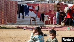 FILE - Syrian refugee children sit at a makeshift settlement in Qab Elias in the Bekaa Valley, Dec. 8, 2014.