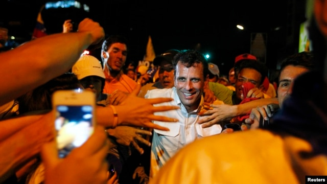 Venezuela's opposition leader and presidential candidate Henrique Capriles (C) greets supporters during a campaign rally in Caracas Apr. 1, 2013.
