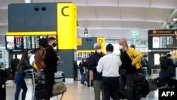 Wisatawan yang memakai masker wajah karena pandemi Covid-19, berdiri di meja check-in di Terminal 2 Bandara Heathrow di London barat pada 21 Desember 2020. (Foto: AFP)