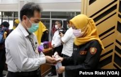 Peserta rapat koordinasi mesti mencuci tangan dengan hand sanitizer dan memakai masker sebelum memasuki ruangan di Pemerintah Kota Surabaya. (Foto: VOA/ Petrus Riski).