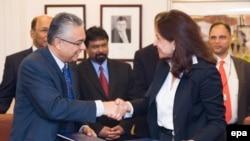 Le vice-Premier ministre et ministre des Finances et du Développement économique de Maurice, Pravind Kumar Jugnauth, à gauche, et le directeur général adjoint du Fonds monétaire international (FMI) Mme Nemat Shafik, à droite, se serrent la main après une cérémonie de signature d'un accord au siège du FMI, à Washington, DC, 18 avril 2011.