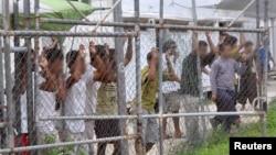 Para pencari suaka mengamati dari balik pagar di pusat penahanan di Pulau Manus, Papua Nugini, 21 Maret 2014 (Foto: dok).