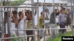 Asylum-seekers look through a fence at the Manus Island detention center in Papua New Guinea, March 21, 2014.