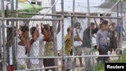 Pencari suaka melihat keluar pagar di kamp penahanan Pulau Manus di Papua Nugini. (Foto: dok.)