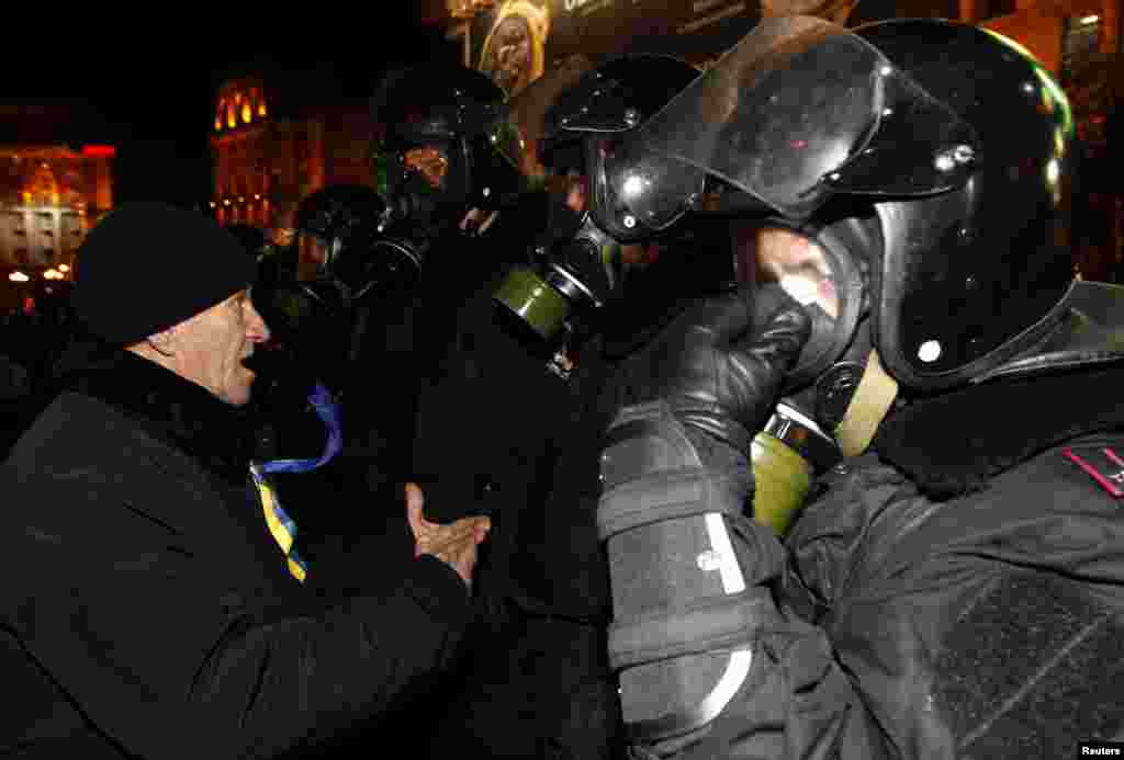 Police stand guard in front of protesters during a demonstration in support of EU integration at Independence Square in Kyiv Nov. 29, 2013.