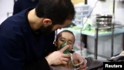 Un homme avec un enfant dans un hôpital de la ville assiégée de Douma, Ghouta orientale, Damas, Syrie 25 février 2018.