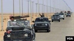 Para pejuang pemberontak Libya mengendarai kendaraan militer mereka di sebelah timur Bani Walid menjelang tenggat bagi loyalis pro-Gaddafi untuk menyerah (8/9).