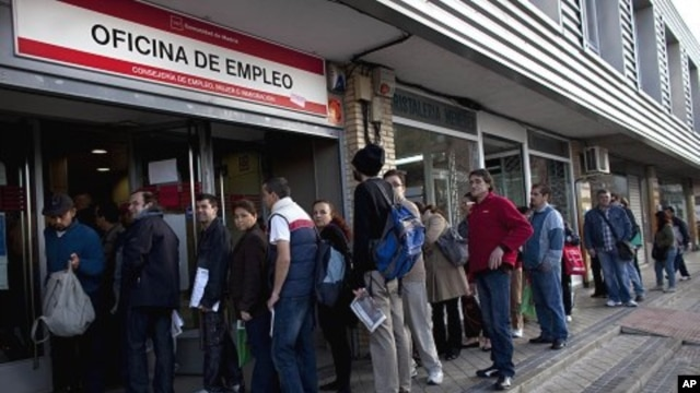 People line up to enter a government employment benefit office in Madrid on Monday, April 4, 2011