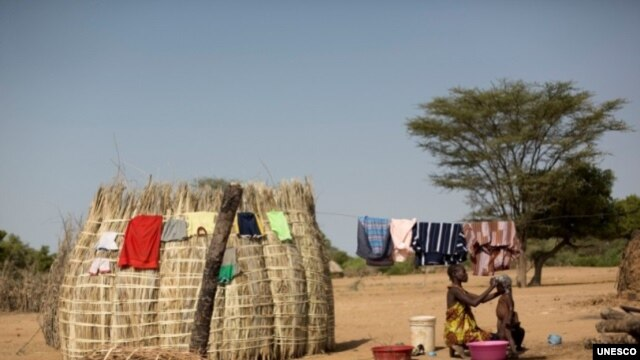 A woman bathes her child next to her hut in Turkana, Kenya. Educating mothers are more likely to seek medical help during pregnancy and childbirth.