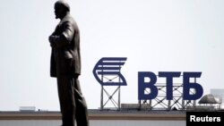FILE - A sign for the logo of VTB Bank on the top of a building is pictured behind a monument of Soviet state founder Vladimir Lenin in Stavropol, Russia, July 17, 2014.