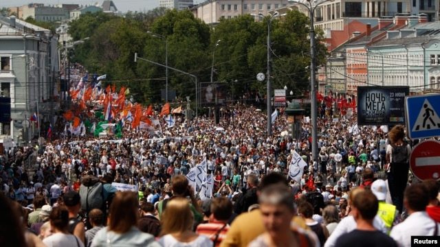Participants march with flags and placards during an anti-government protest in Moscow