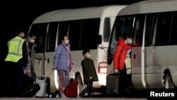 Công dân Úc đến từ thành phố Vũ Hán của Trung Quốc, tâm dịch Covid, lên xe bus tại phi trường trên đảo Christmas, Australia, ngày 6/2/2020.
