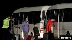 Warga Australia yang dievakuasi dari kota Wuhan, menuju bus yang akan membawa mereka ke tempat enampungan sementara setibanya di bandara Pulau Christmas, Australia, 6 Februari 2020.