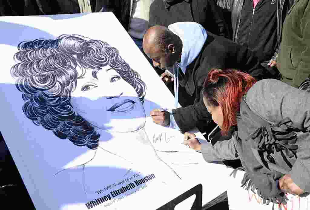 Para penggemar menulis di sebuah poster bergambarkan Whitney Houston dekat lokasi upacara penghormatan terakhir bagi Houston di Gereja New Hope Baptist di Newark, New Jersey, 18 Februari 2012 (AP).