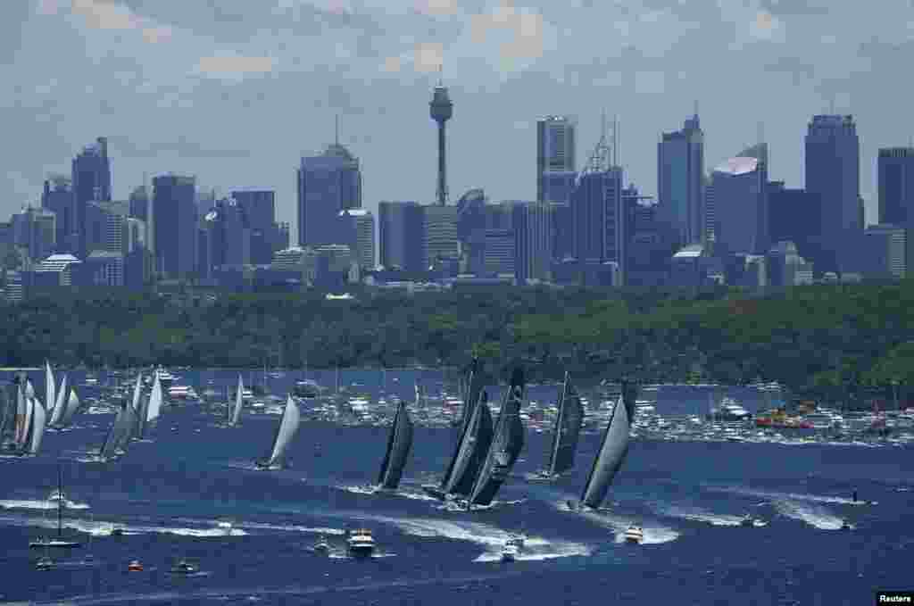 The field of yachts head down Sydney Harbor at the start of the annual Sydney to Hobart yacht race, Australia.