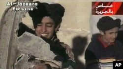In this image made from a video broadcast by Al-Jazeera, Nov. 7, 2001, a young boy, left, identified as Hamza bin Laden holds what the Taliban says is a piece of U.S. helicopter wreckage.